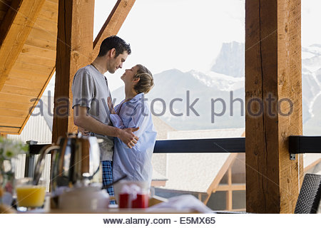 Couple hugging on balcony with mountain view - Stock Photo