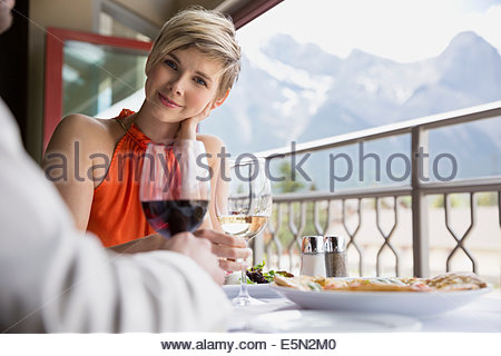 Woman drinking wine at restaurant table on balcony - Stock Photo