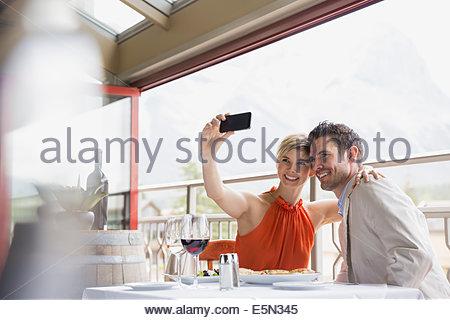 Couple taking selfie at restaurant table on balcony - Stock Photo