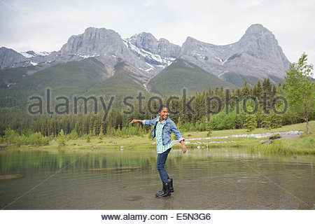 Girl playing in lake with mountains in background - Stock Photo