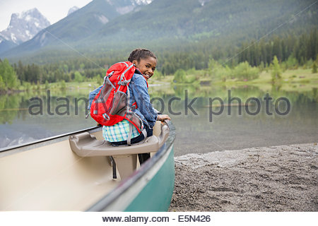 Girl with backpack in canoe at lake - Stock Photo