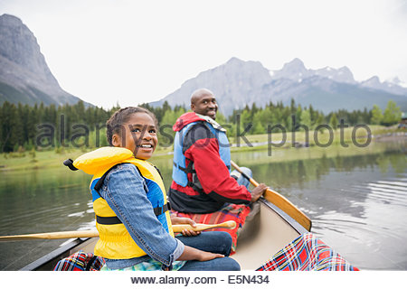 Father and daughter canoeing in lake - Stock Photo