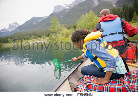 Father and daughter fishing in canoe on lake - Stock Photo