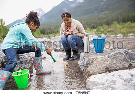 Mother and daughter fishing at stream - Stock Photo