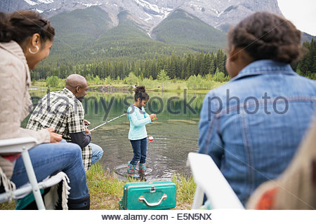 Family fishing at lakeside below mountains - Stock Photo