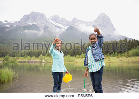 Portrait of sisters holding small fish in lake - Stock Photo