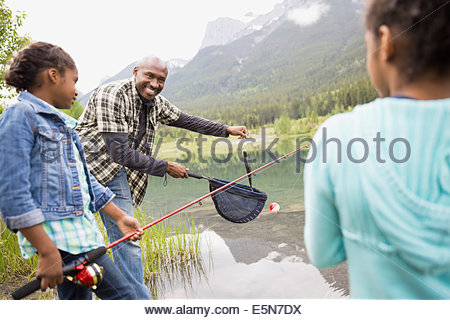 Father and daughters fishing at lakeside - Stock Photo