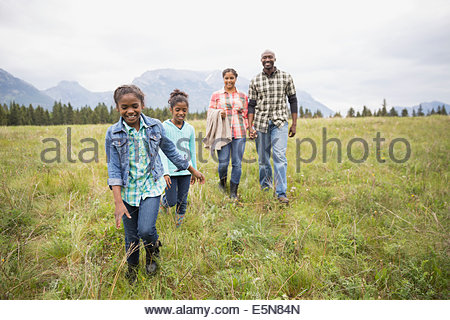 Family walking in grassy field - Stock Photo