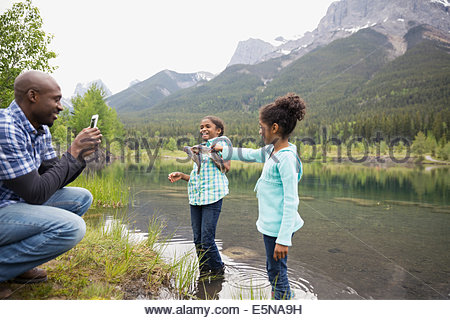 Father photographing daughters with fish in lake - Stock Photo