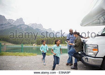 Family with map at RV near lake - Stock Photo