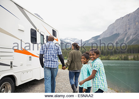 Family at lakeside walking toward RV - Stock Photo