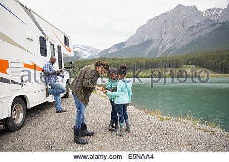 Family standing at lakeside near RV - Stock Photo