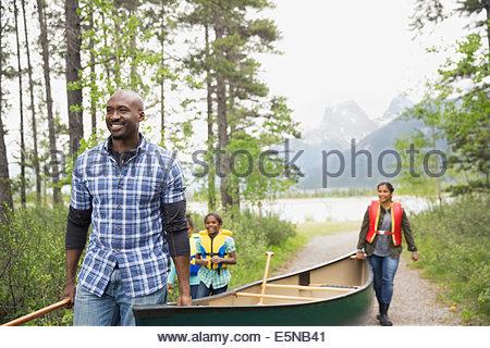 Family carrying canoe away from lake - Stock Photo