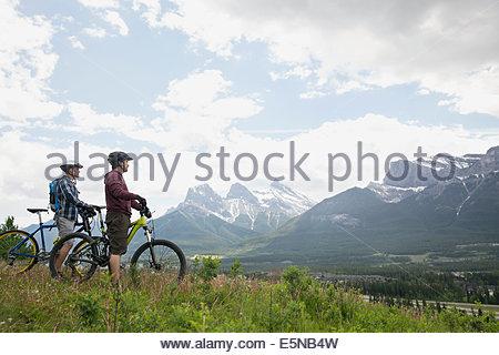 Men on mountain bikes looking up at mountains - Stock Photo