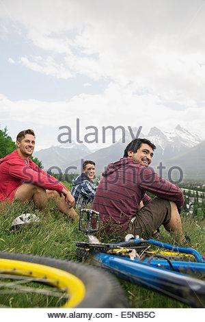 Men with mountain bikes sitting in grass - Stock Photo