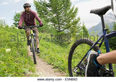 Men riding mountain bikes on trail - Stock Photo