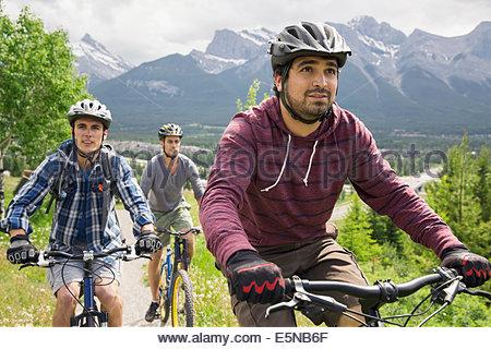 Men riding mountain bikes below mountain - Stock Photo