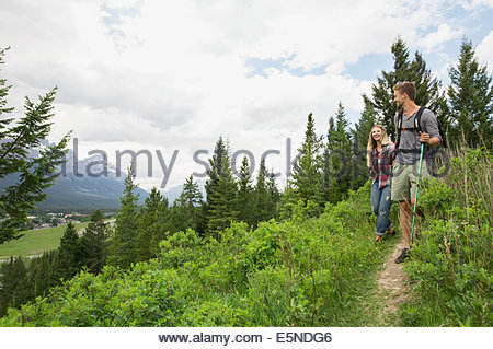 Couple hiking on trail near mountains - Stock Photo