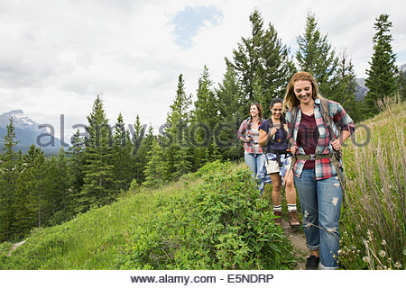 Friends with backpacks hiking on trail - Stock Photo