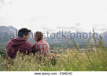 Couple sitting in grass with mountain view - Stock Photo