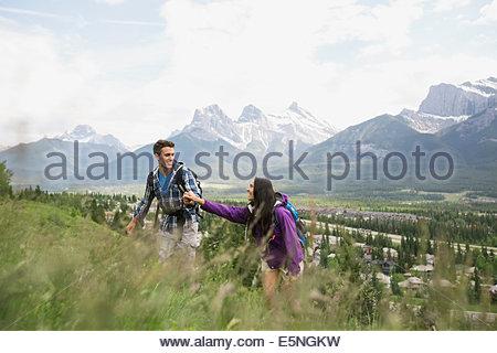 Couple hiking on hillside near mountains - Stock Photo
