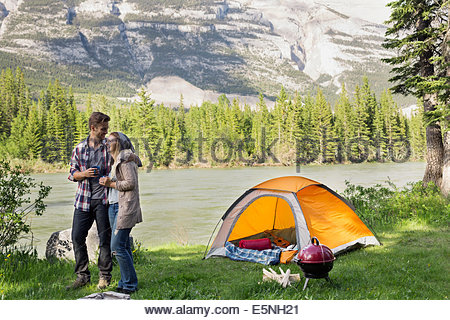 Couple camping at lakeside - Stock Photo