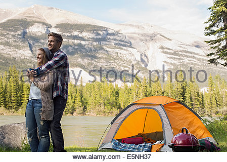 Couple hugging outside campsite at lakeside - Stock Photo