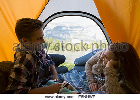 Couple laying in tent with mountain view - Stock Photo