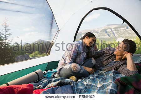 Couple talking in tent with mountain view - Stock Photo