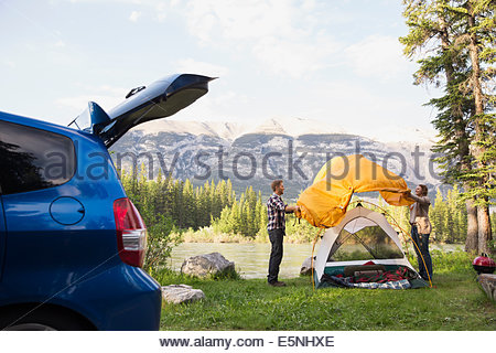 Couple assembling tent at campsite near mountains - Stock Photo