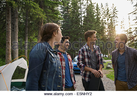 Friends talking at campsite - Stock Photo