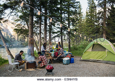 Friends hanging out at lakeside campsite - Stock Photo