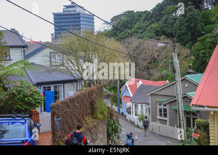 residential steep housing location in wellington  new zealand with man and child walking down the steep road. - Stock Photo