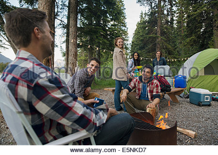 Friends hanging out around campfire at campsite - Stock Photo