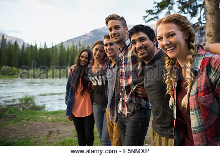 Portrait of friends in a row at lakeside - Stock Photo