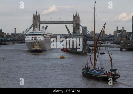 London,UK. 4th August 2014. Luxury cruise ship Silver Cloud passes under Tower Bridge after docking next to HMS - Stock Photo