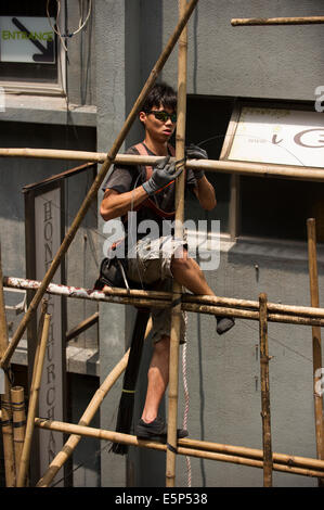 Hong Kong worker tying bamboo together to create a scaffold. - Stock Photo
