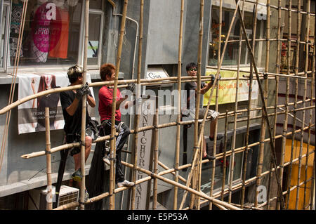 Hong Kong workers tying bamboo together to create a scaffold. - Stock Photo