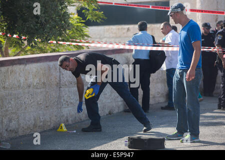 Jerusalem. 4th Aug, 2014. Israeli security personnel mark the scene where a man riding on a motorcycle opened fire - Stock Photo