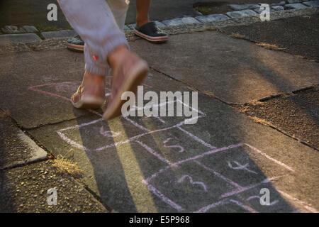 Child playing hopscotch on marked out chalk on a pavement, London, UK - Stock Photo