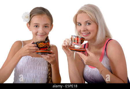 Mother and daughter drinking tea from painted tea things - Stock Photo