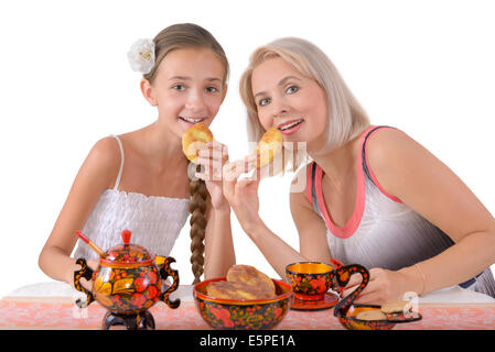 Mother and daughter eating pies on the white background - Stock Photo