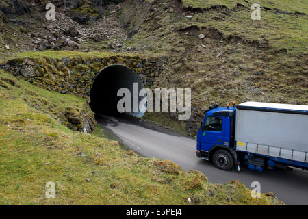 Truck driving into a single-track tunnel between Husar and Mikladalur, Kalsoy, Faroe Islands, Denmark - Stock Photo