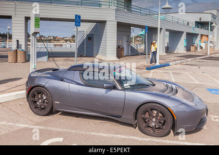 Tesla Roadster plugged in to a public re-charging point on the pier at Santa Cruz, California. - Stock Photo