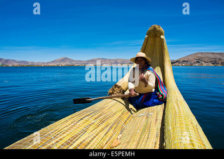 Local in a traditional rowing boat of Totora reed on Lake Titicaca, Peru - Stock Photo