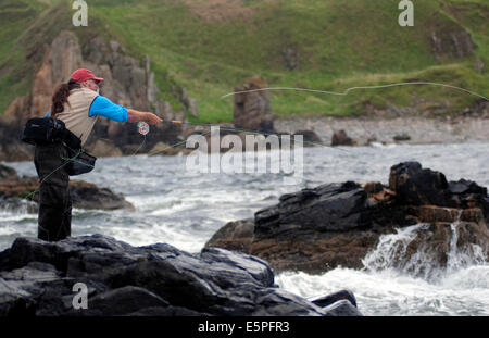 Salt water fly fisherman Dave Felce casting a fly fishing rod into the sea off the East coast of Scotland - Stock Photo