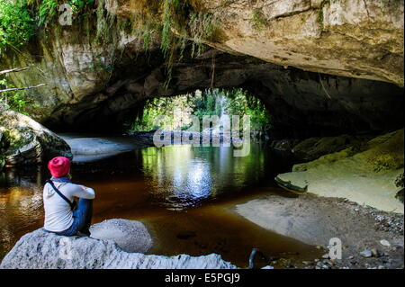 Woman enjoying the stunning Moria Gate Arch in the Oparara Basin, Karamea, West Coast, South Island, New Zealand, - Stock Photo