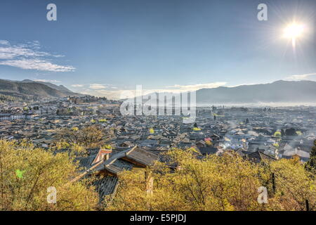 A view over the Old Town part of Lijiang, UNESCO Site, and surrounding mountains on a clear morning, Lijiang, Yunnan, - Stock Photo