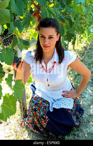 Young woman holding a grape in her hand - Stock Photo