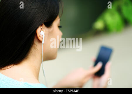 Closeup portrait of a woman in headphones listening to music with her smartphone - Stock Photo